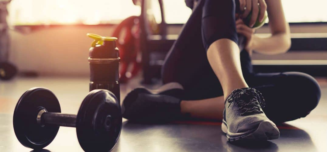 Woman resting next to sports bottle and dumbbell in gym