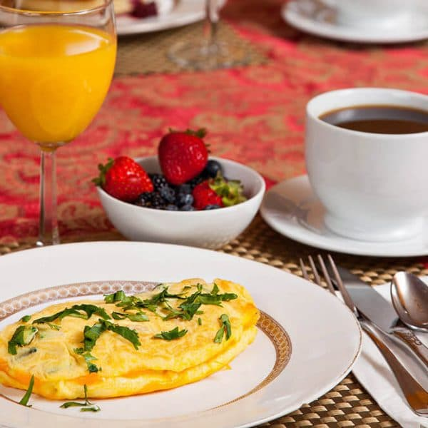 Omelette with juice, fruit, and coffee