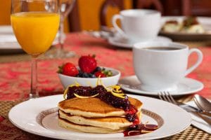 Pancakes with fruit, juice, and coffee