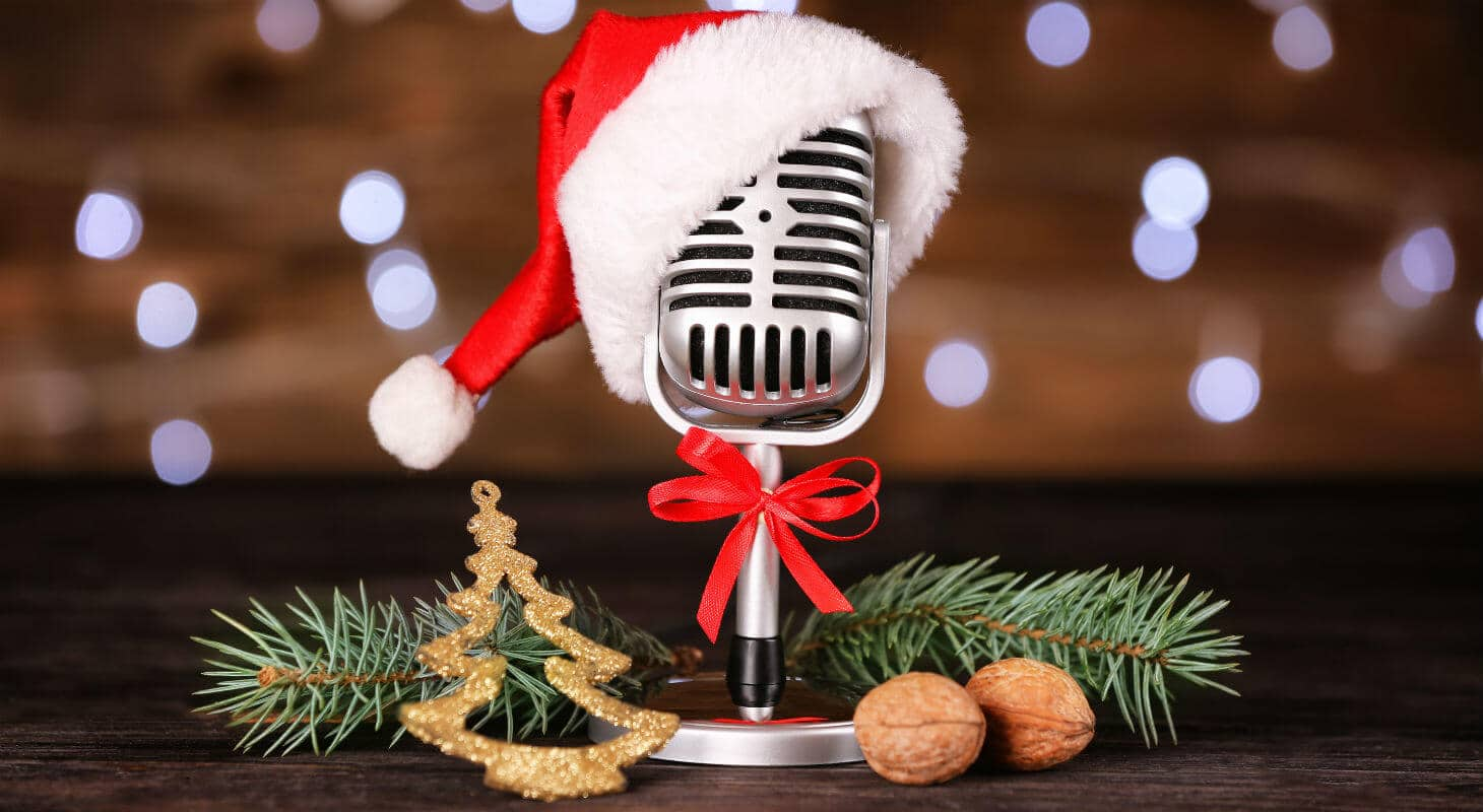Vintage microphone wearing Santa hat next to pine boughs and chestnuts