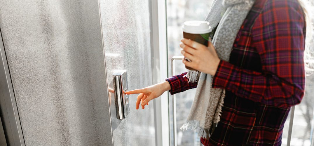 Woman presses elevator button to ride up to observation deck while holding coffee