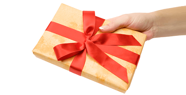 Hand holding a gold gift box with red bow