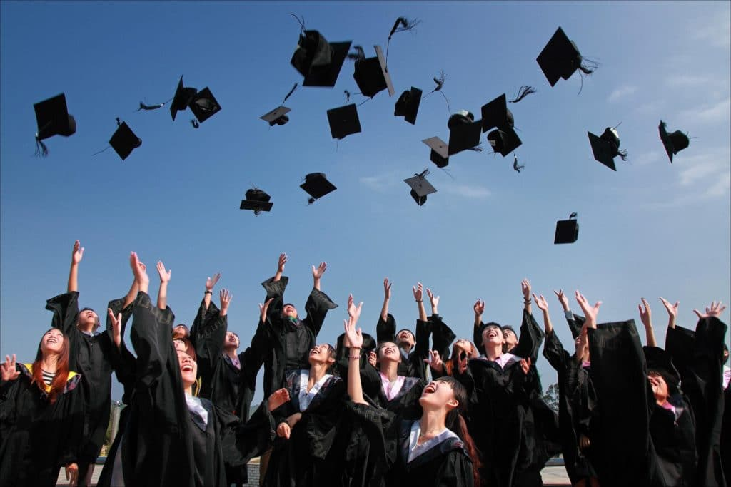 Students tossing graduation caps into the air