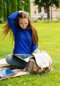 Student studying on the lawn