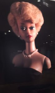 Levinthal photograph of a Barbie with short, perfectly coiffed hair. She is wearing pearls and a black dress.