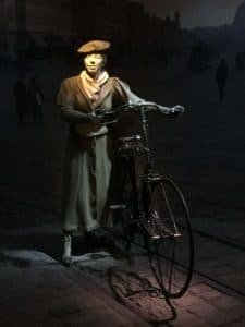 Woman in a skirt and hat pushing a bicycle.