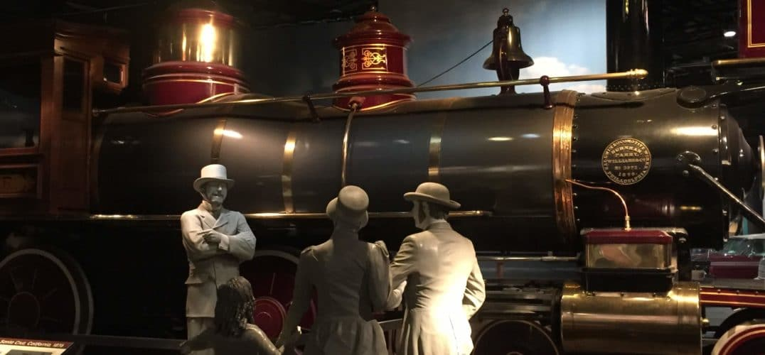 Three adults and a child conversing in front of an old fashioned train engine.