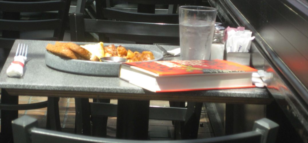 A table in the cafe with a plate of food, a glass of water and a book.