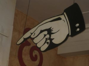 A sign in the shape of a hand pointing a finger