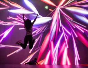Girl Jumping in Front of Vibrant Colored Art