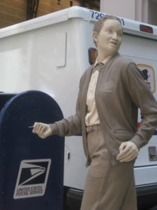 Statue of a postal worker standing in front of a mail box and mail truck.