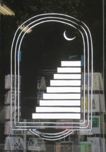 Black and white logo featuring ascending stairs viewed through an archway.