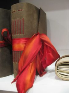 Leather journal tied with a red-orange ribbon