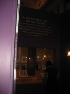 A visitor to the exhibit examining a display beneath a suffrage quote.