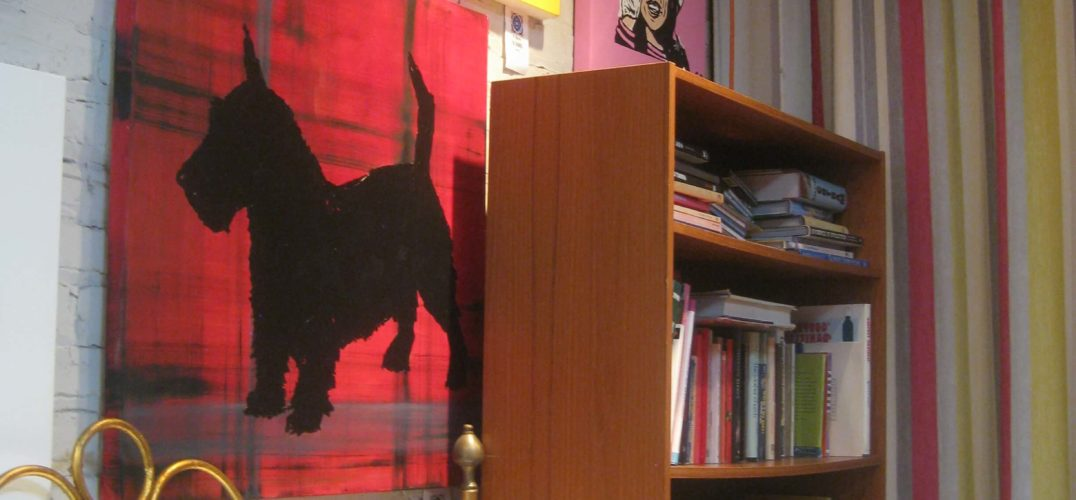 Picture of a painting of a Scottie dog next to a bookshelf