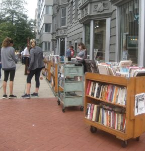 People inspecting books on carts outside.