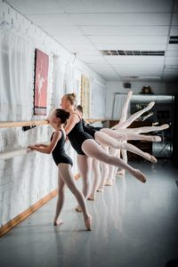 Row of girls stretching at a ballerina bar