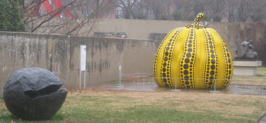 Sculptures. One is a metal sphere, the other is a yellow pumpkin with black spots