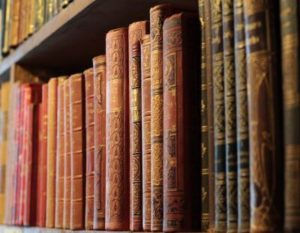 Historical and classical books are displayed on an antique bookshelf
