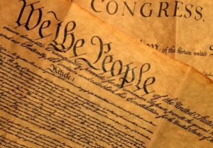"""The Constitution of the United States is shown with the words """"We the People"""" displayed"""