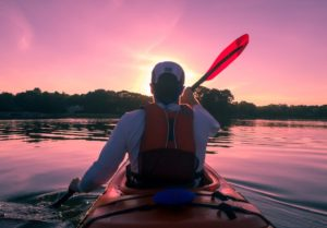 a man sits alone in a kayak. the sun sets in front of his face. our view, from the camera, is from directly behind his head, with his head blocking the sun. He is in a red kayak wearing a white breathable bent brim hat, a white long sleeve shirt, a life vest (orange) and the sun is casting a pink hue over the sky and the water as it sets. He is facing some trees on the shore.