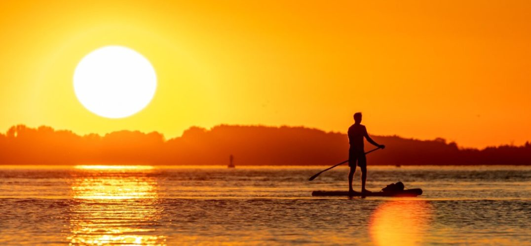 a man stands up on a paddleboard. the sun is setting in the sky over a row of trees behind him. we can see the row of trees outline the shore of the river he is on. It could also be a lake, the water is relatively calm. A lens flare marks the bottom of the image, giving it a dreamy quality.