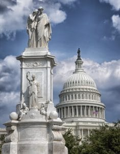 The United States Capitol Building behind a white statue of two people