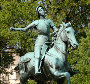 Copper staue of Joan of Arc on a horse, with the green patina of age