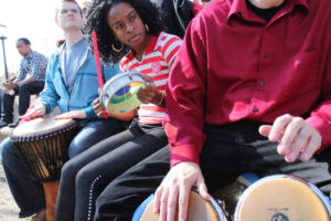 People sitting on a low wall, holding drums in a drum circle