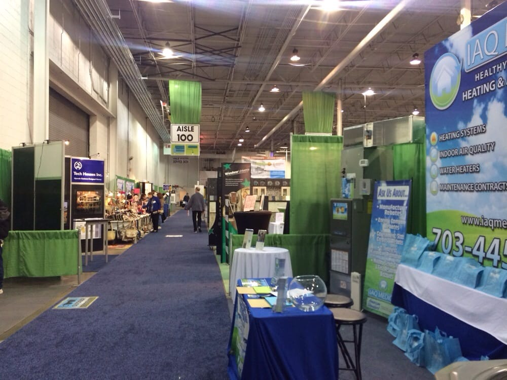 Interior of expo center, blue carpeting throughout with green curtains separating displays.