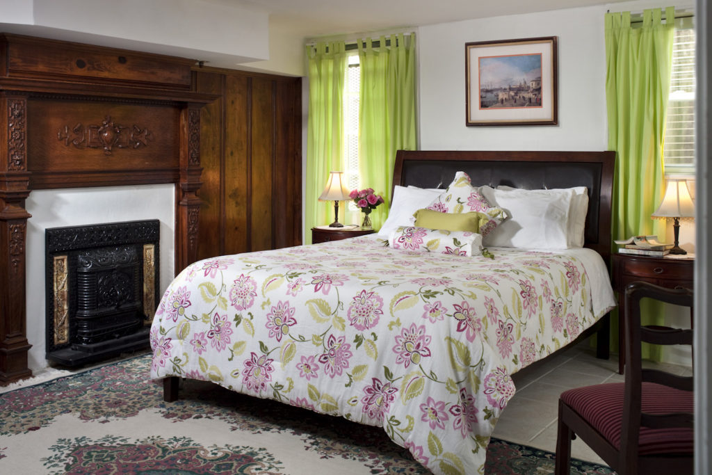 Beautiful gruest room with floral bedding, light green curtains, and a fireplace