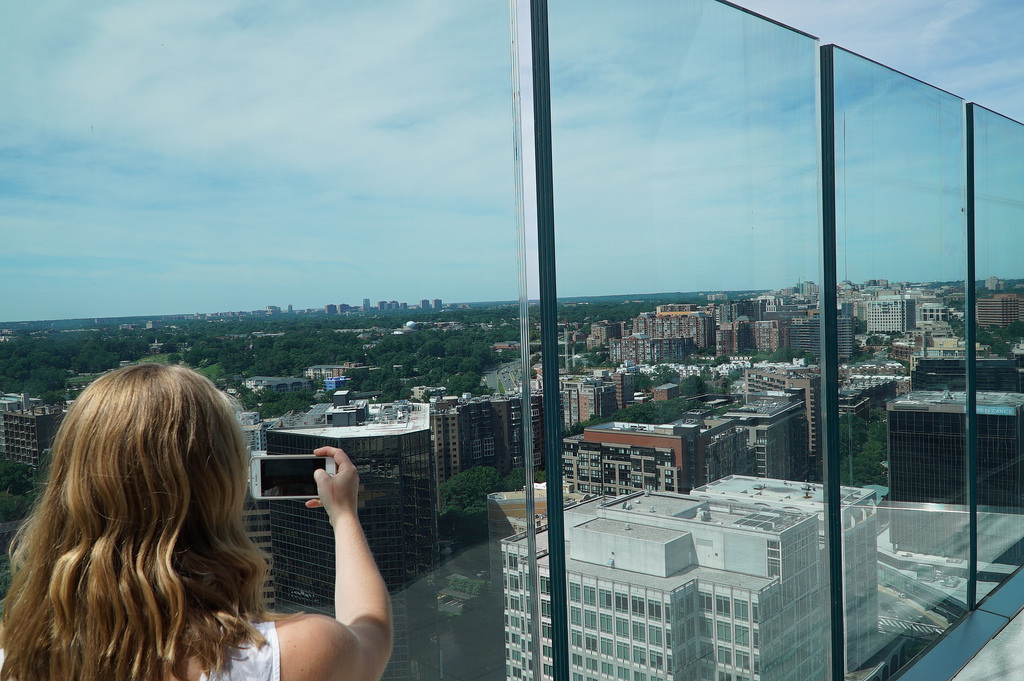 Blonde woman taking a photo looking out into the city through large windows.
