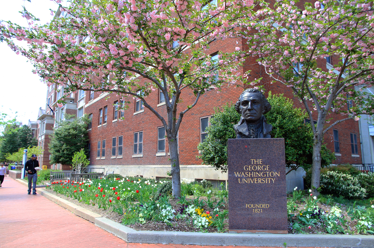 Attractive landscaping in front of red brick building with a sign in front that says George Washington University