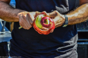 A man's hands peeling a red apple at the state fair