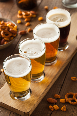 Flight of beer from gold to amber to dark cocoa colored, surrounded by scattered pretzels