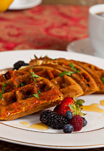 Four waffle quarters arranged on china plate with berries and syrup