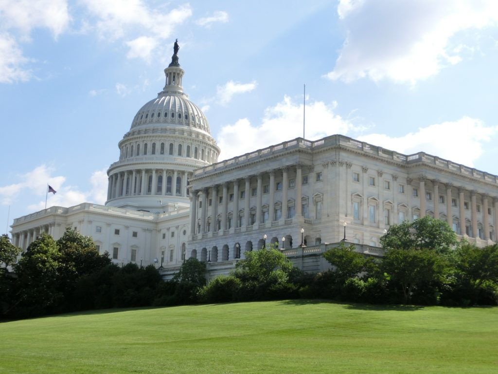 Corner view of the beautiful, white, US Capitol building surrounded by expansive green lawn and blue skies
