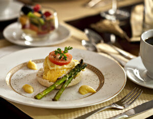 Eggs benedict on china plate with asparagus and tomato