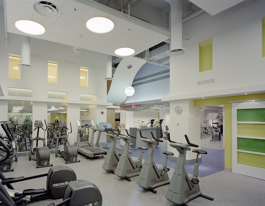 Workout bikes and treadmills in an office building with white walls and gray carpeting.