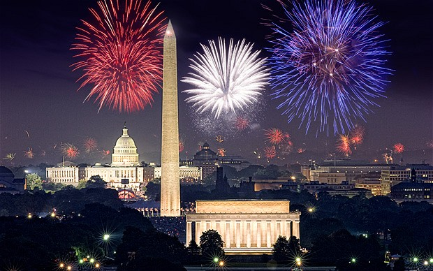 Red white and blue fireworks bursting over the nation's Capitol, the Lincoln Memorial, and Washington Monument