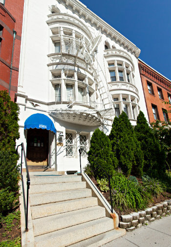 White building with a blue awning in row of brownstones