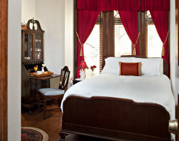 Large room with red drapes, wrting desk and bed with white coverings
