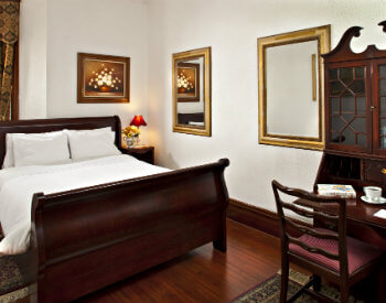 Wood floors, white walls, wood sleigh bed with white cover