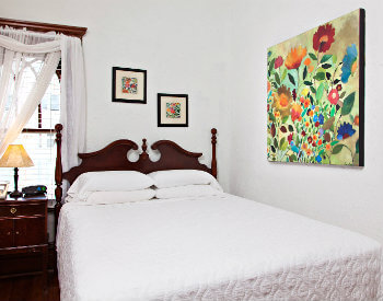 Bright white room with colorful paintings on wall