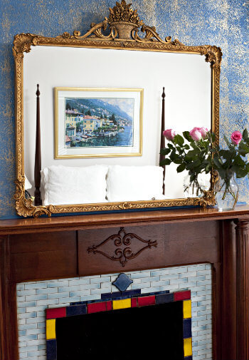 Lovely old fireplace with colorful surround and gilt mirror