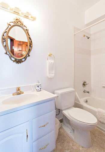 All white bathroom with gold framed mirror and tub/shower combo