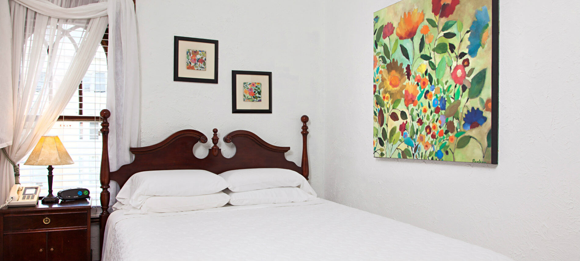 White airy room with wooden bed with light cover