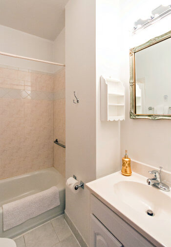 White bathroom with tiled shower/tub combo and gold-trimmed mirror over sink