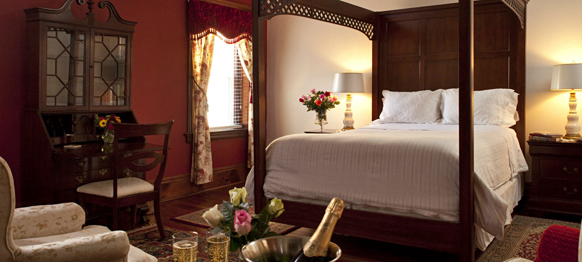 Large elegant room with four-poster bed and burgundy walls