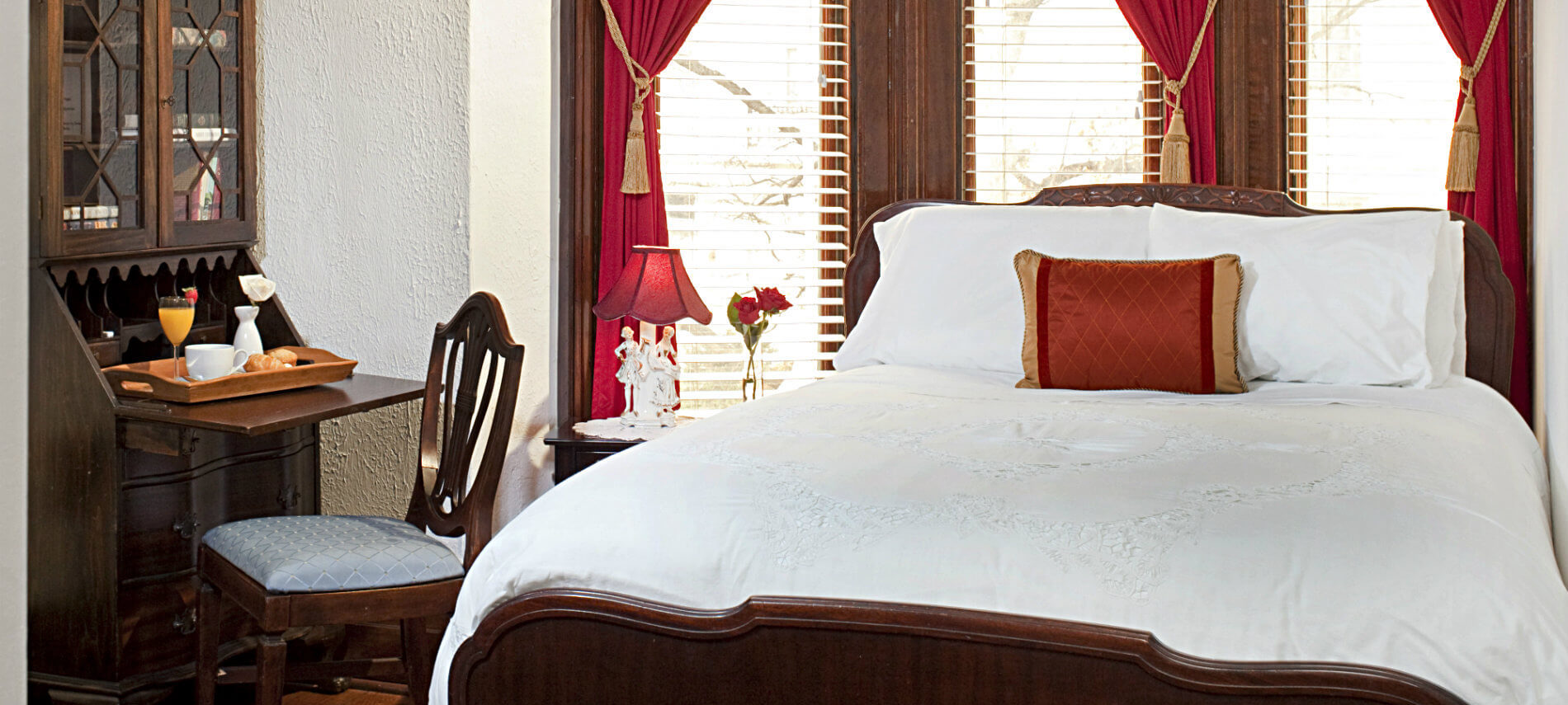 Large wooden bed covered with white with a big window behind it